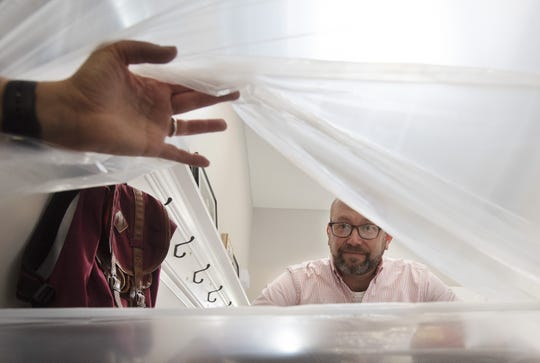 David Miller of Chippewa Township talks to his wife, Mary Ann Miller,  through a slit in a plastic barrier that keeps him isolated from family during his two-week quarantine. Miller, a licensed funeral director and embalmer, assisted overwhelmed colleagues in New York City with burials of COVID-19 victims.