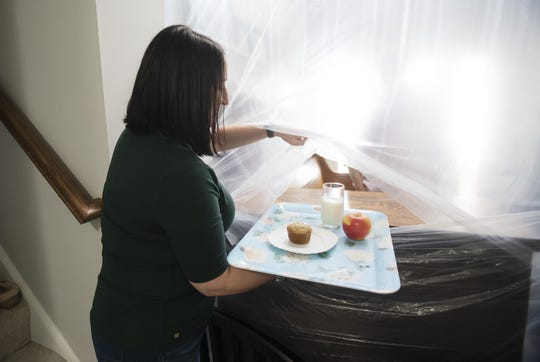 Mary Ann Miller of Chippewa Township slides a tray of food to her husband, David Miller, through a slit in a plastic barrier that keeps him apart from the rest of his family during his two-week quarantine. Miller, a licensed funeral director and embalmer, recently returned from 10 days in New York City and Long Island where he and a colleague transported bodies of COVID-19 victims from hospitals to funeral homes. He is now isolated in a small area of his home.