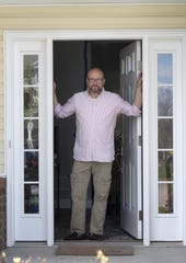 "David Miller of Chippewa Township stands at the front door of his condo. Miller said his 14-day quarantine after spending 10 days in a COVID-19 hot spot in New York has made him ""appreciate human interaction a lot more. It makes me miss 'normal.'"""