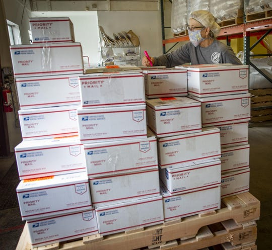 Camas Country Mill co-owner Sue Hunton marks an order after placing it on a pallet with other retail orders prepared for shipping. The mill has seen their retail orders skyrocket in the wake of Covid-19 closures.