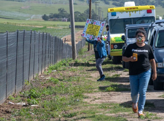 "A woman holds a sign that reds ""Gracias amigos campesinos"" which translates to ""Thank you our farmworker friends"" a girl wearing a ""Decolonize"" shirt walks next to her during the Salinas Farmworker Appreciation Caravan on Saturday, April 25, 2020."