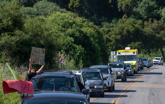 "A girl holds a sign that reads ""Gracias por su trabajo y su esfuerzo!"" which translates ""Thank you for your work and effort"" as a line of cars follows behind on Saturday, April 25, 2020."