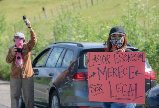 "Marlene Garcia, right, holds a red sign that reads ""labor Esencial merece ser legal"" during the Salinas Farmworker Appreciation Caravan in Salinas, Calif, on Saturday, April 25, 2020."