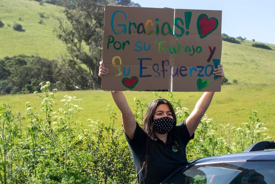 "A girl holds a sing that reads ""Gracias por su trabajo y su esfuerzo!"" which translates ""Thank you for your work and effort"" as a line of cars follows right behind on Saturday, April 25, 2020."