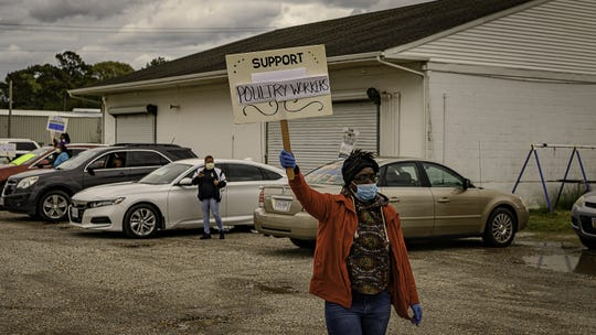 A protester holds up a sign in support of poultry workers at the rally site across the street from the Perdue Plant in Accomac.
