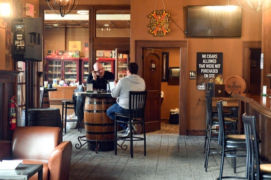Patrons smoke cigars and talk in an otherwise empty room on Tuesday, April 28, at Stogeez Cigar Club in Sioux Falls.
