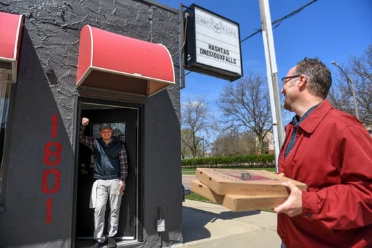 Sunny's Pizzeria owner Jon Oppold greets Ryan White from afar as he picks up his order on Tuesday, April 28, 2020 in Sioux Falls, S.D. The pizza restaurant is offering no contact curbside pickup to prevent the spread of the coronavirus.