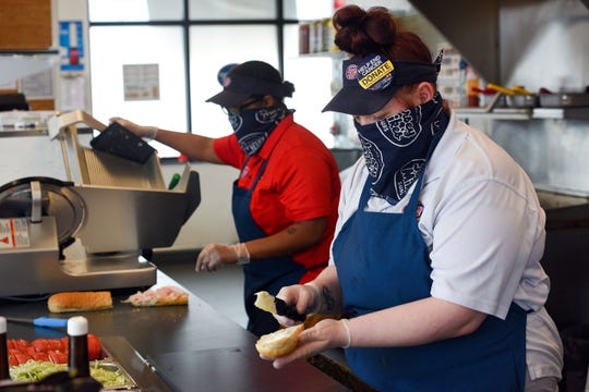 Employees make a to-go order while wearing branded bandanas as face coverings on Tuesday, April 28, at Jersey Mike's in Sioux Falls.