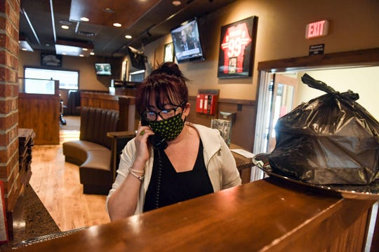 Lindsey Hillberg, general manager, takes a curbside pickup order over the phone on Tuesday, April 28, at Cherry Creek Grill in Sioux Falls.
