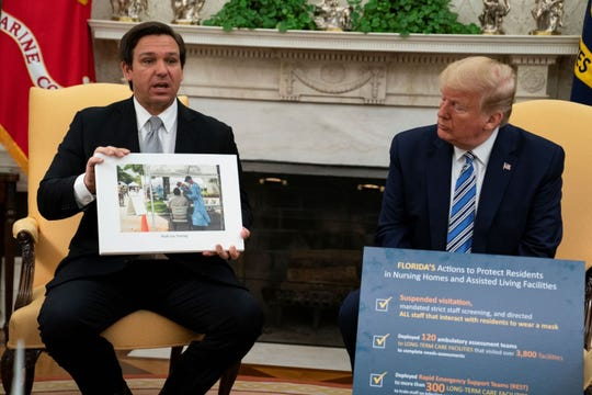President Donald Trump listens as Gov. Ron DeSantis, R-Fla., talks about the coronavirus response during a meeting in the Oval Office of the White House, Tuesday, April 28, 2020 in Washington.
