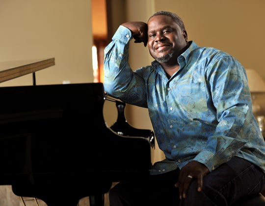 Gospel singer and producer Troy Sneed sits at the piano in the living room of his Orange Park home in January 2013. Sneed died of the coronavirus at age 52.