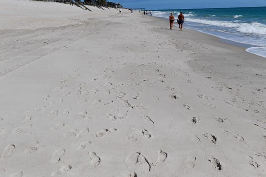 Footprints are left in the sand on Tuesday, April 28, 2020, as community members walk along the beach near Jaycee Park in Vero Beach. On Tuesday, Indian River County officials re-opened the public access points after they had closed them because of the spread of the novel coronavirus. Beach activities are limited to running, walking, surfing and exercise and social distancing measures are still in place.