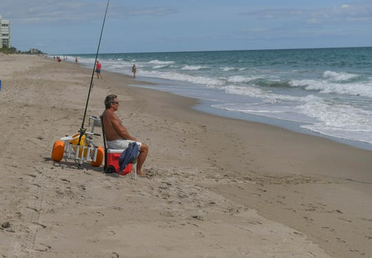 """Joel Johnston, of Jensen Beach, fishes from the shoreline of Dollman Park Beachside Beach on Tuesday, April 28, 2020, in southern St. Lucie County. """"It's awesome, enjoying the weather, the sunshine, I'm glad the beaches are back open,"""" Johnston said. After more than a month the beaches in St. Lucie County are now open, with restrictions, to help prevent the spread of the COVID019 virus. Activities that allow for social distancing include, limiting groups to less than 10 people, and staying 6 feet apart, are permitted. Activities include: walking, jogging, surfing, paddleboarding, kayaking, swimming, fishing, and shell collecting."""