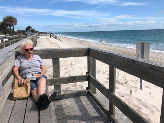 Trudi Berger, 85, of Vero Beach, snacks on a McDonald's breakfast burrito as she takes in the view from Jaycee Beach Park in Vero Beach on  April 28, after the beaches opened for the first time since closed over COVID-19 concerns.