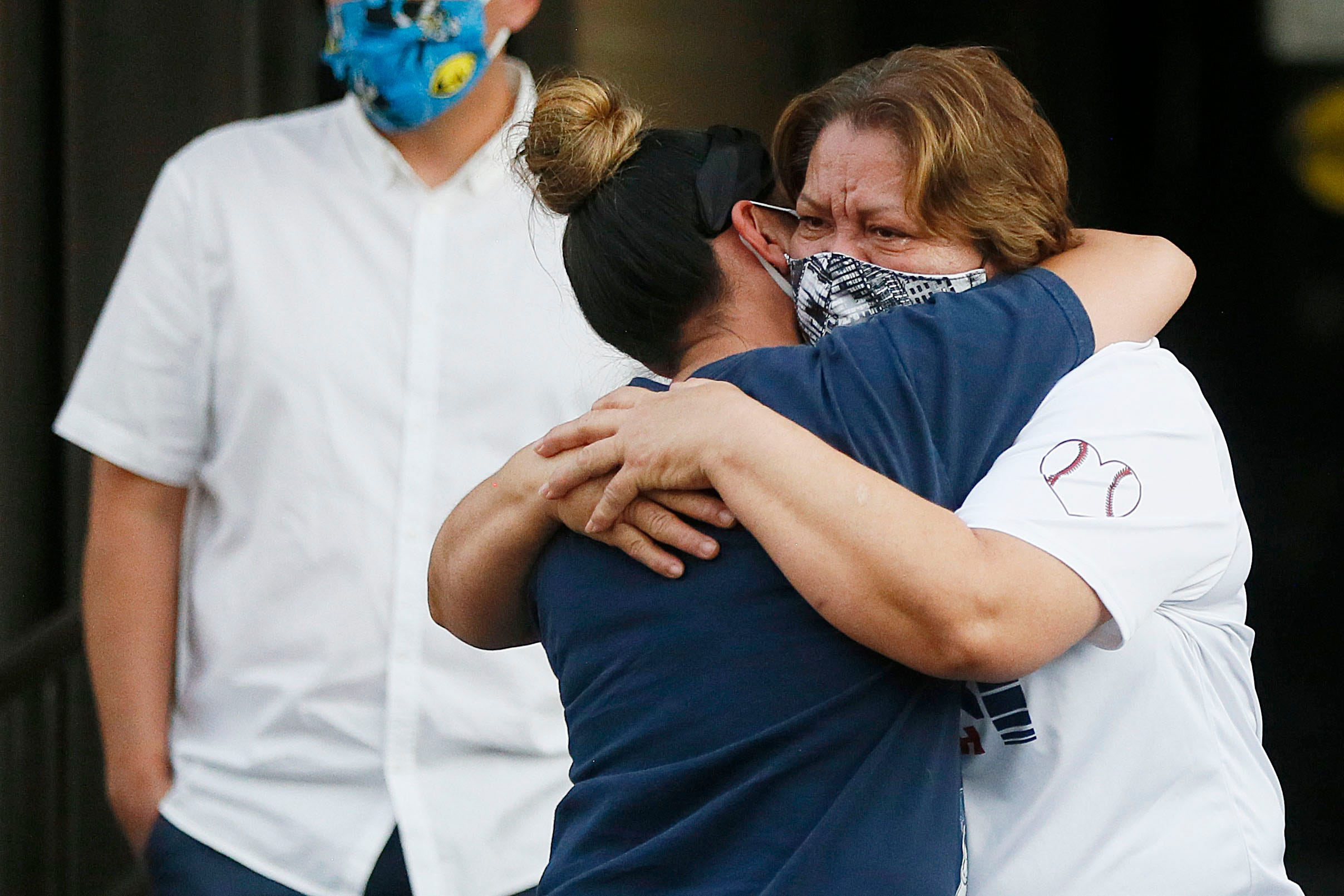 """El Pasoans hug at a drive-through prayer vigil for Guillermo """"Memo"""" Garcia on Monday, April 27, at Del Sol Medical Center in El Paso. Garcia died on Saturday after beinghospitalized at Del Sol Medical Center for nearly nine months. He was shot on Aug. 3 in what federal prosecutors have described as a domestic terror attack."""