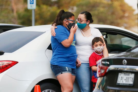 "Jessica Garcia holds her daughter Karina and son Guillermo during the drive-thru prayer vigil for Guillermo ""Memo"" Garcia Monday, April 27, at Del Sol Medical Center in El Paso. Garcia died on Saturday after beingÊhospitalized at Del Sol Medical Center for nearly nine months after being shot on Aug. 3 in what federal prosecutors have described as a domestic terror attack."