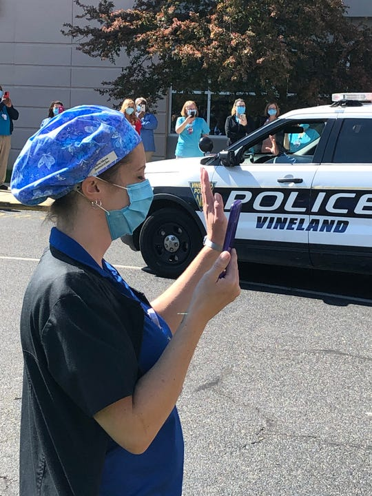 Police officer waves to an Inspira Medical Center Vineland healthcare worker during a procession to offer support  during the COVID-19 panademic. April 28, 2020