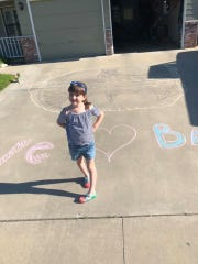 Elodie Monteiro patiently awaits Batman's arrival on Monday in her east Tulare driveway.