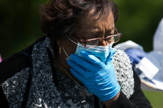 A woman covers her face after taking a coronavirus test Tuesday, April 28, 2020, at the Route 9 Library in New Castle.