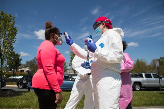Healthcare workers screen residents who believe they have symptoms of the coronavirus Tuesday, April 28, 2020, at the Route 9 Library in New Castle.