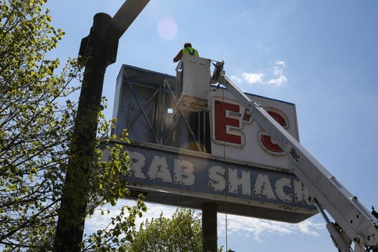 Workers dismantle the Joe's Crab Shack sign on Wilmington's riverfront on Tuesday, April 28. The restaurant is permanently closed after 17 years of operation.