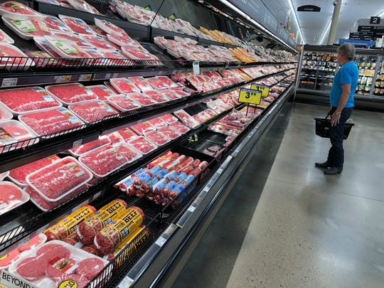 A shopper surveys the overflowing selection of packaged meat in a grocery early Monday, April 27, 2020, in southeast Denver. With closures in meat processing plants across the country because of the spread of the new coronavirus among workers, food analysts are forecasting shortages of beef, pork and poultry on the shelves of the country's supermarkets in the days ahead. (AP Photo/David Zalubowski)