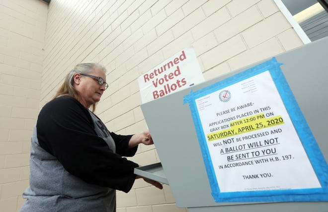 Andrea Harmon of Chandlersville places her ballot in the dropbox outside the Muskingum County Board of Elections on Tuesday.