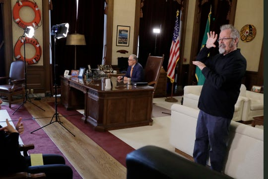 American Sign Language interpreter Terry Dockter, right, signs as Washington Gov. Jay Inslee sits at his desk and rehearses a speech on April 21.