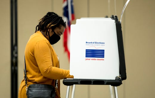 A person wears a mask to protect against the coronavirus,  votes in the Ohio primary election at the Hamilton County Board of Elections on Tuesday, April 28, 2020, in Norwood, a suburb of Cincinnati.