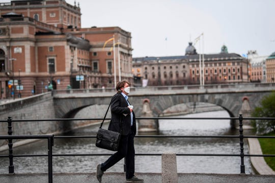 A man wearing a protective mask walks in the rain past the Royal Swedish Opera (at left) in Stockholm, Sweden, on April 27, 2020.