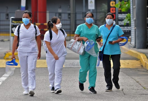 Health workers walk out from the Convention Center, where the municipality set up a field hospital for people infected with the new coronavirus, in Guayaquil, Ecuador on April 28, 2020.