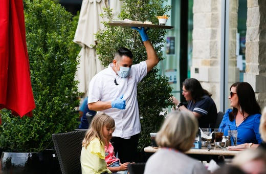 A waiter at Gloria's Latin Cuisine in serves up lunch to patrons on the patio in Colleyville, Texas on April 27, 2020.