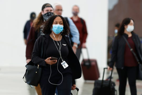 Passengers, most wearing face masks, enter the main terminal after arriving at Denver International Airport on April 23, 2020.