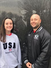 Ava Guillot and her father Jonathan Guillot, great-granddaughter and grandson of Gene Guillot, pose with a photo of Gene as a young sailor that is etched in the Korean War Memorial in Washington D.C.