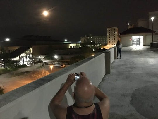Jackson Sleet (front) and Shana Prince Lazarone chased the pink moon that appeared on April 7 to the top of the public parking garage in downtown Alexandria to take photos.