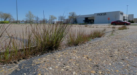 Grass grows through cracks in the parking lot at the closed Ocean County Mall in Toms River Tuesday, April 28, 2020.