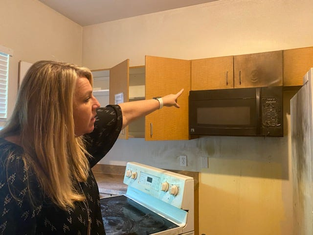 Beverly DeMeyer, president of Serene Harbor, points out fire damage in the kitchen area.