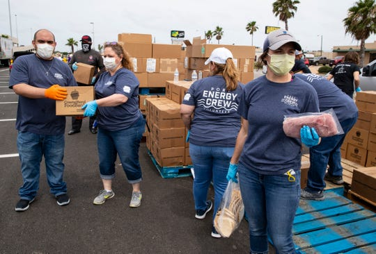Volunteers load food in to cars during the Costal Bend Food Bank's pop up food distribution in the La Palmera parking lot on Wednesday, April 29, 2020.