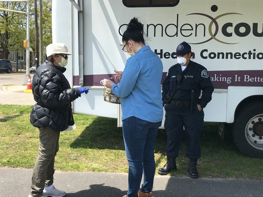 Irma Santiago offers a mask to a woman in East Camden. City and county officials said the neighborhood is a hot spot for COVID-19, and they will open a testing site there early next week.