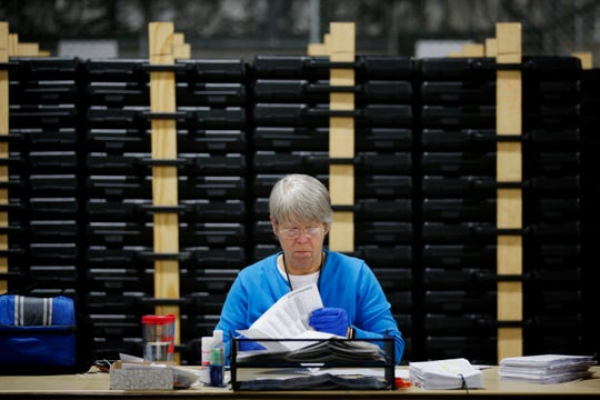 Election workers open and verify ballots as they send them along in the counting process at the Hamilton County Board of Elections on April 28, 2020.