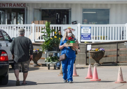 Customers make their way to their cars with plants and flowers after shopping at Goode Greenhouse in Des Moines on Wednesday, April 29, 2020.