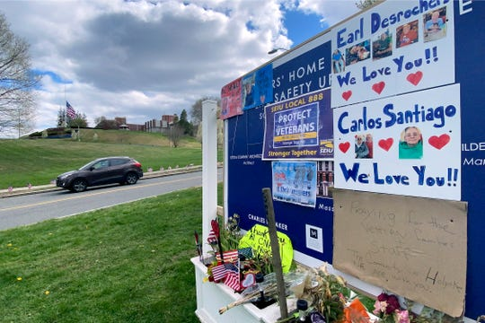 Tributes to veterans cover a sign Tuesday, April 28, 2020, near an entrance road to Soldiers' Home in Holyoke, Mass., where a number of people died due to the coronavirus.