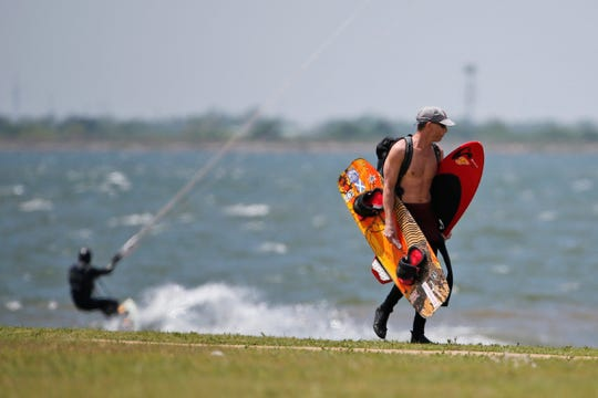 A kiteboarder carries his gear at Lake Hefner, Monday, April 27, 2020, in Oklahoma City.