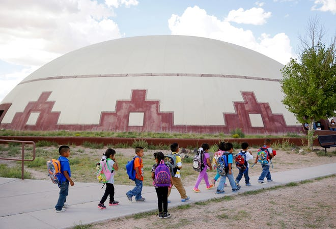 FILE - In this Sept. 25, 2014, file photo, students walk between buildings at the Little Singer Community School in Birdsprings, Ariz., on the Navajo Nation. The tribe is among plaintiffs in a federal lawsuit that seeks to keep the U.S. Treasury Department from disbursing coronavirus relief funding for tribes to Alaska Native corporations.