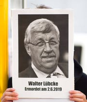 In this June 18, 2019 file photo, an activists of the Antifa, anti-fascism action, shows a poster of Walter Luebcke during a protest against right-wing violence in Berlin, Germany, Tuesday, June 18, 2019.