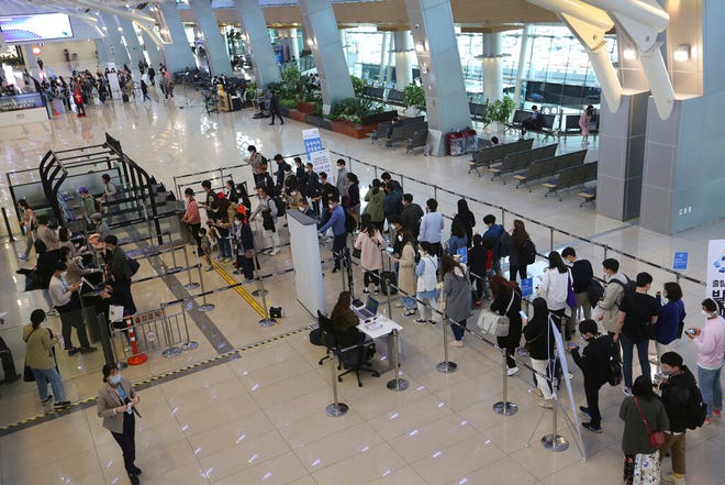Passengers wait in line before boarding their planes at the domestic flight terminal of Gimpo airport in Seoul, South Korea, Wednesday, April 29, 2020. South Korean officials have issued public pleas for vigilance to maintain hard-won gains against the coronavirus as the nation enters its longest holiday since infections surged in February.