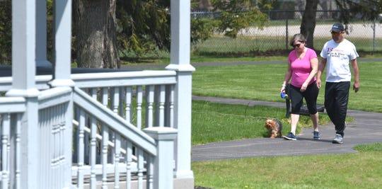 Karyn Montalvo and her husband, Jaime Montalvo, both of Washington Township walk their six-year-old male Yorkie named, 'Louie,' at Washington Community Park in Washington Township.