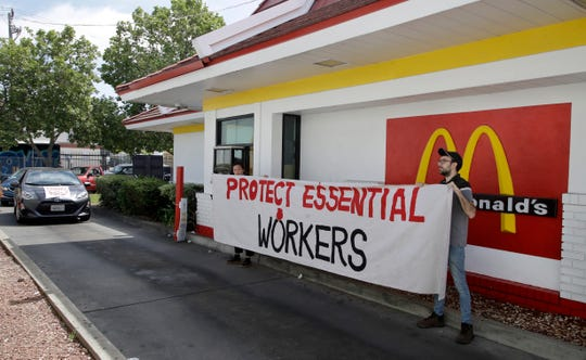 FILE - In this April 21, 2020, file photo, people protest what they say is a lack of personal protective equipment for employees as they close down the drive-thru at a McDonald's restaurant in Oakland, Calif.