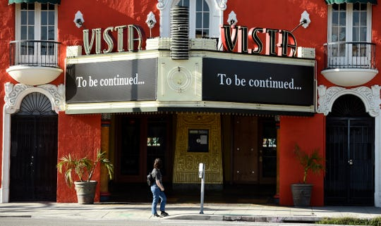 """A pedestrian looks up at a """"To be continued..."""" message on the marquee of the Vista movie theatre, April 21, 2020, in Los Angeles. Movie theaters remain closed as stay-at-home orders continue in California due to the coronavirus pandemic."""