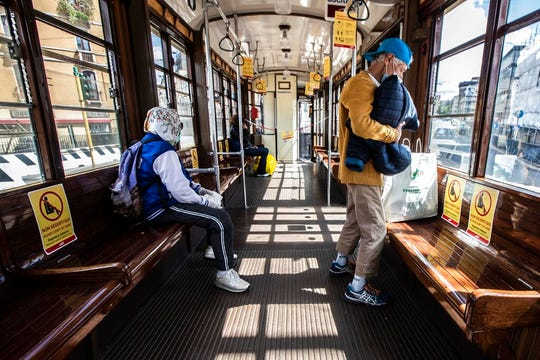 People sits on a tram as signs reading 'please don't sit here, respect social distancing', are seen on the benches, in Milan, Italy, Wednesday, April 29, 2020.